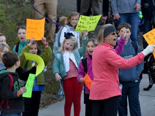 Anne Crais, front, watches for traffic before crossing street to West Hills Elementary School Wednesday, April 13, 2016 as West Hills residents and students rallied to get the city to build sidewalks along Sheffield Drive.