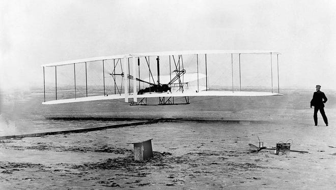 FILE--Orville Wright, at the controls of the Wright Flyer, and his brother Wilbur watches from the ground during the plane's first flight at Kitty Hawk, N.C., Dec.17, 1903.  Made of wood, wire and cloth by the two bicycle mechanics, the plane remained aloft for 12 seconds and traveled a distance of 120 feet. (AP Photo/File)