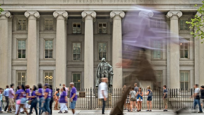 Pedestrians and tourists go about their usual lunchtime routine in front of the United States Treasury headquarters building in Washington, Friday, as the U.S. government and the financial markets analyze and react to Britain's vote to withdraw from the European Union.