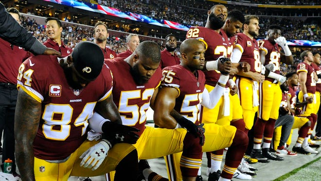 Washington Redskins tight end Niles Paul (84) and linebackers Ryan Anderson (52) and Chris Carter (55) kneel with teammates during the playing of the national anthem before the game against the Oakland Raiders at FedEx Field.