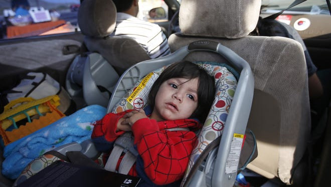 Jaden Rosales, 1, of Phoenix, waits with his parents, Anthony and Rosales for a free new car seat during an event in February 2015.