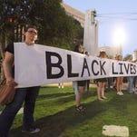Ligia Arguilez, left, helps hold a long banner during an El Paso Black Lives Matter Vigil Sunday night in San Jacinto Plaza.