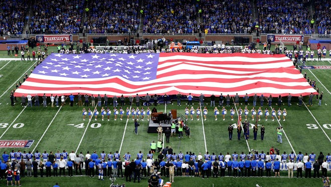 Nov 24, 2016; Detroit, MI, USA; Patrons display the American flag on the field during the national anthem performed by Aretha Franklin before the game between the Detroit Lions and the Minnesota Vikings at Ford Field.