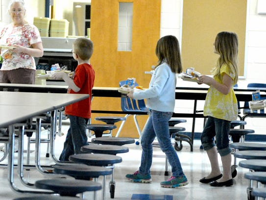 Standing in line, students carry their trays forward