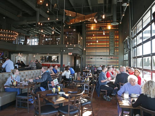 Garage doors open to outdoor area at Four Day Ray Brewing,