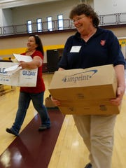 From left, Sierra Lobato, a Salvation Army store manager, and Sandra Liebel, social services director for the agency, carry boxes on Thursday as they help set up for the annual San Juan County Homeless Veterans Stand Down, which will take place Friday at San Juan College's Health and Human Performance Center in Farmington.