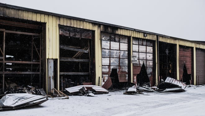 Snow falls in front of the Power Train automotive parts facility along U.S. 40 in New Paris, Ohio, on Tuesday, Dec. 26, 2017, less than two days after the building was gutted by a large fire.