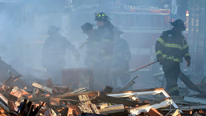 Kansas City firefighters look over the aftermath of a building fire Tuesday in Kansas City.  Two firefighters involved in rescuing two residents from a burning building died after a wall collapsed on them, authorities said.