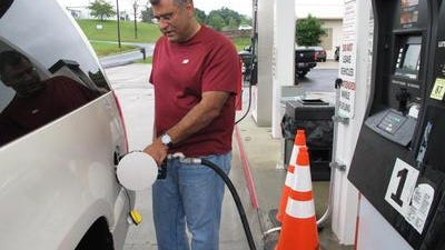 Samir Cook fills up his vehicle in Somerset, Ky. Gas prices are inching as low as $1.85 per gallon in Greater Cincinnati.