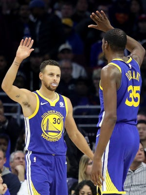 Stephen Curry #30 and Kevin Durant #35 of the Golden State Warriors celebrate during the end of the Warriors 124-116 win over the Philadelphia 76ers.