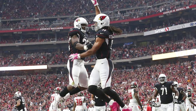 Arizona Cardinals wide receiver Larry Fitzgerald (right) celebrates his touchdown catch with Arizona Cardinals running back Adrian Peterson (23) against the Tampa Bay Buccaneers during the second quarter at University of Phoenix Stadium in Glendale, Ariz. October 15, 2017.