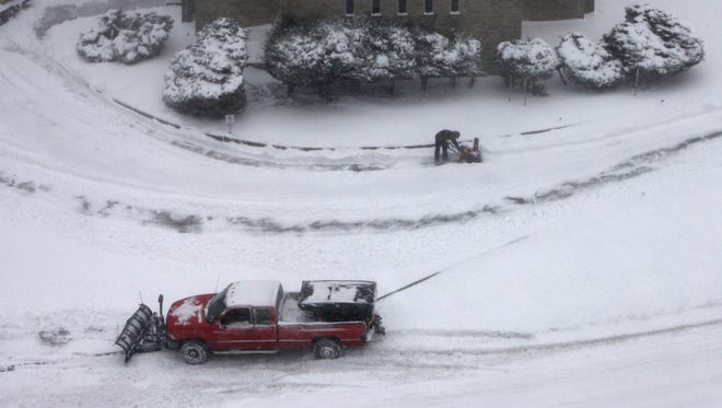 Workers with New York Property Services in Yonkers clear the sidewalks and driveway at the New Testament Church on Saturday.