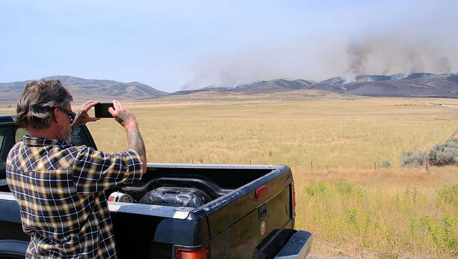 Danny Nickle takes a picture of a wildfire Thursday, Aug. 4, 2016, near Plymouth, Utah. Officials say more than two dozen large wildfires are burning in the West.