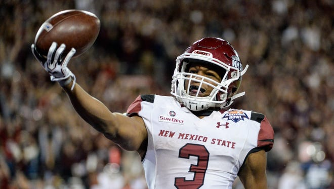 New Mexico State Aggies running back Larry Rose III (3) scores the game-winning touchdown against the Utah State Aggies in overtime in the 2017 Arizona Bowl at Arizona Stadium.