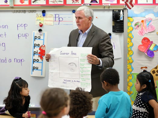 Indiana Governor Mike Pence thanks students for a hand-drawn picture of him while visiting the pre-school classes at Shepherd Community Center, 4107 E. Washington Street on Wednesday, February 26, 2014. Pence is passionate about the importance of legislature passing a pre-school voucher pilot program, a proposal which has been changed in the Senate to a study commission.