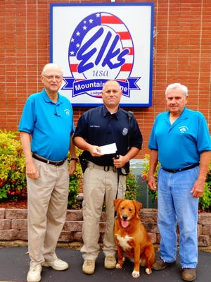 Mountain Home Elks Lodge 1714 presents $500 to the Mountain Home Police Department School Resource Officer Drug Detection Canine program. Shown are, from left, Don Swanson, Elks lodge president; Eddie Helmert, school resource officer; Bomber, MHPD K-9; and John Browning, Elks drug-awareness chairman. The canine drug-detection program is a joint effort between Mountain Home Public Schools and the Mountain Home Police Department for intervention to assist in the prevention of substance abuse by local youth.