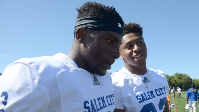 Former Salem star running back Jonathan Taylor, right, chats with Zaire Jones on the sideline after Jones scored one of his two touchdowns in Saturday's 20-18 win over Penns Grove.