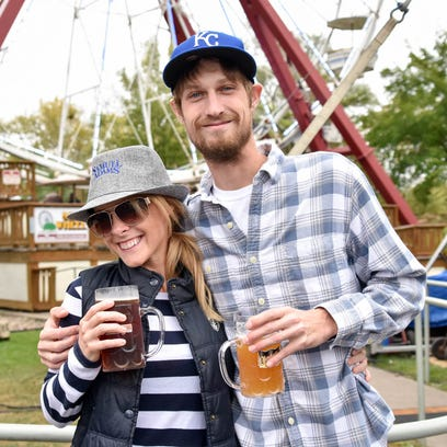 Jessica Wemple, 30, and Kyle Watson, 26, both of Windsor Heights, drink by the Ferris wheel Saturday, Oct. 1, 2016, at Adventureland Oktoberfest in Altoona.