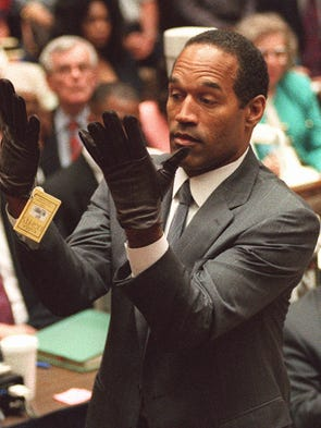 "** FILE **In this June 21, 1995 file photo, O.J. Simpson holds up his hands before the jury after putting on a pair of gloves similar to the infamous bloody gloves during his double-murder trial in Los Angeles. A sports memorabilia dealer who profited off O.J. Simpson alleges the football star confessed to murdering his ex-wife and says in a new book that he helped him outwit prosecutors with the gloves. ""How I Helped O.J. Get Away With Murder: The Shocking Inside Story of Violence, Loyalty, Regret and Remorse,"" hits stores Monday, May 12, 2008.  (AP Photo/Vince Bucci,File Pool)"
