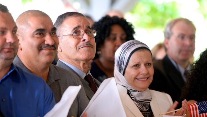 Petitioners show emotion after listening to the singing of the national anthem before taking the Oath of Citizenships. They are among 80 individuals who became U.S. citizens during a naturalization ceremony at the Frontier Culture Museum on Wednesday, Sept. 17, 2014.