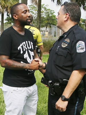 D'Angelo Gary and Fort Myers Police Lt. Roger Valdiva talk shop during the March for Unity event Sunday in the Dunbar community of Fort Myers. More than 150 people walked through Dunbar in an effort to promote peace.