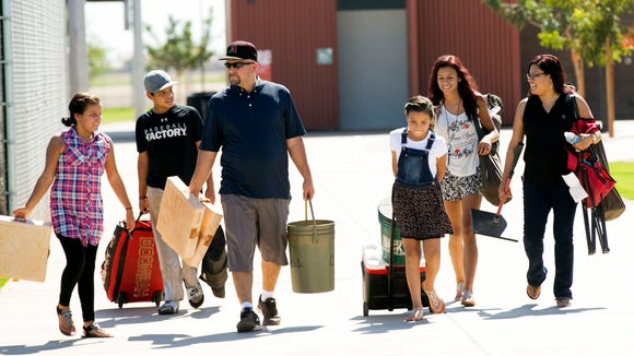 Lynn Andrews, 33, of Maricopa, walks with his children Helen Andrews (from left), 10, Lynn Andrews, 12, Mariah Andrews, 9, and Lynniece Andrews,14, and wife Deniece Andrews after Lynn Andrews coached Lynn's little league practice at the Copper Sky Recreation Complex in Maricopa.