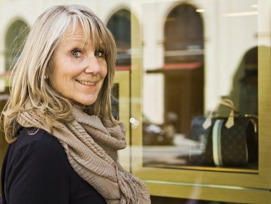 Smiling older woman window shopping
