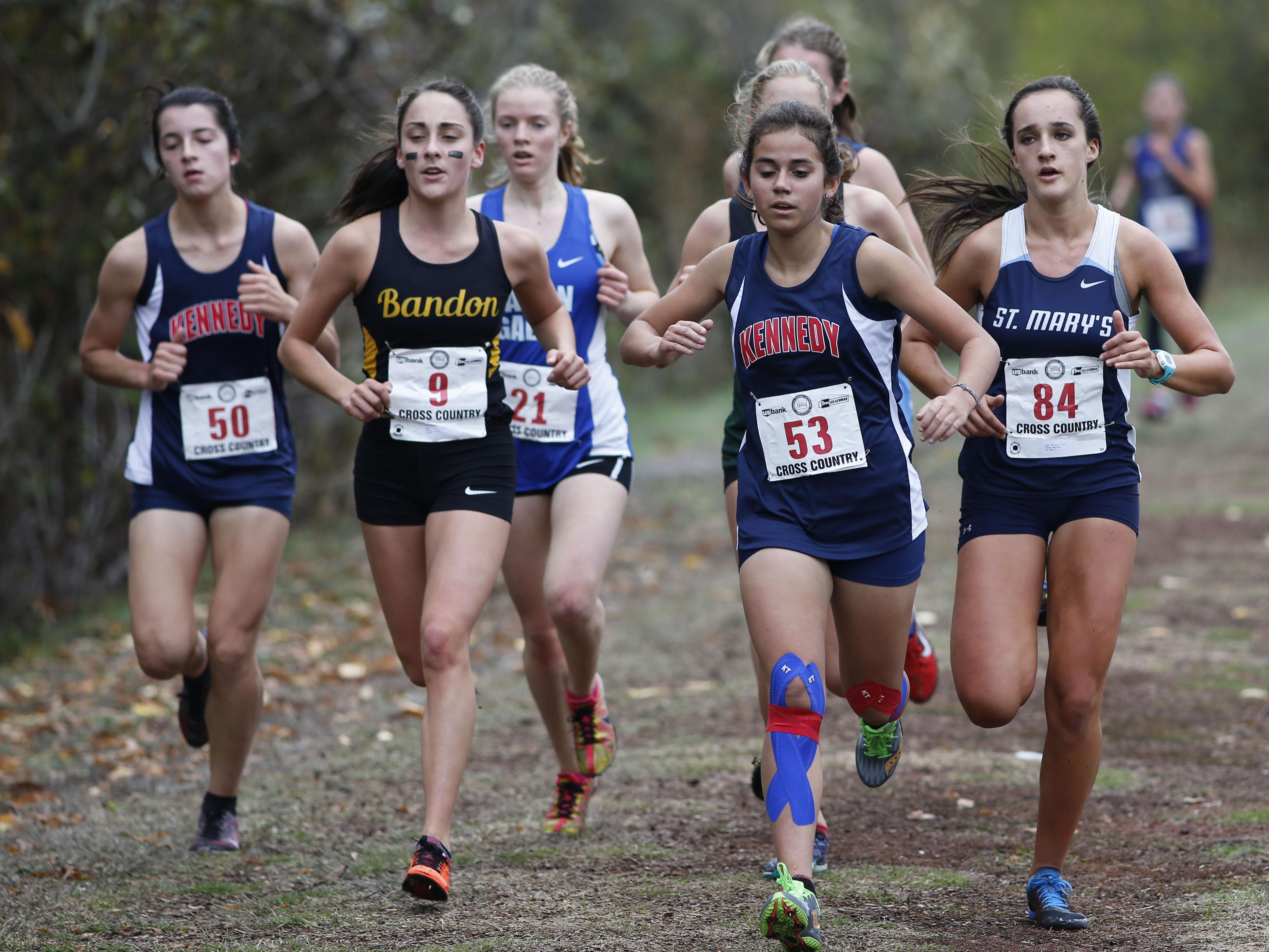 Kennedy's Alejandra Lopez, front right, and Kaylin Cantu, left, competes in the 3A/2/1A state cross country championships at Lane Community College on Saturday, Oct. 31, 2015. (Timothy J. Gonzalez/For the Statesman Journal)