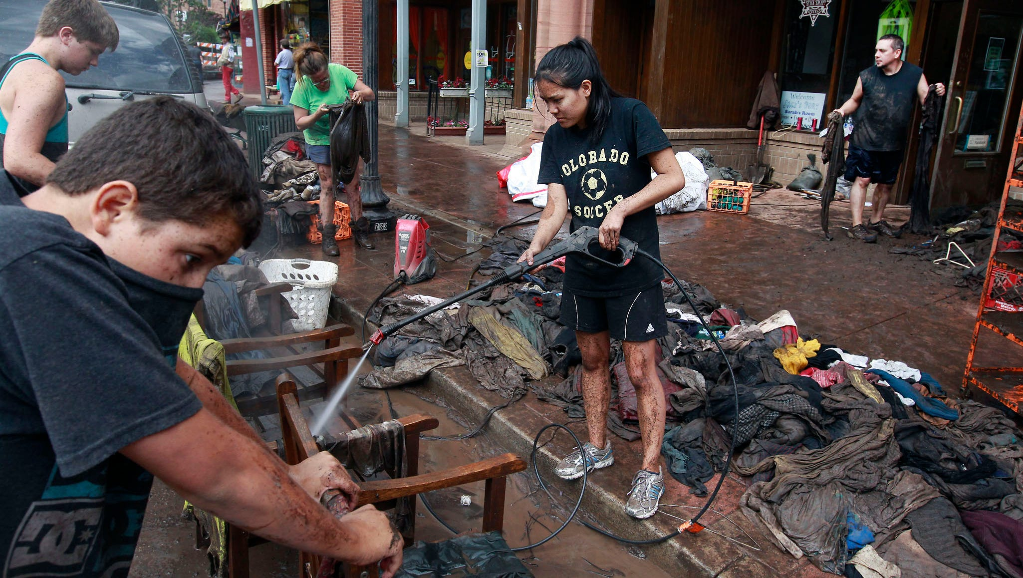 Alex Caffery, center, helps local wash mud off merchandise at a store that was damaged in the flash flood.