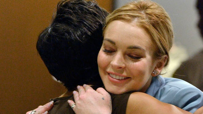 Lindsay Lohan, right, embraces her attorney, Shawn Chapman Holley after a progress report on her probation for theft charges at Los Angeles Superior Court on March 29, 2012.