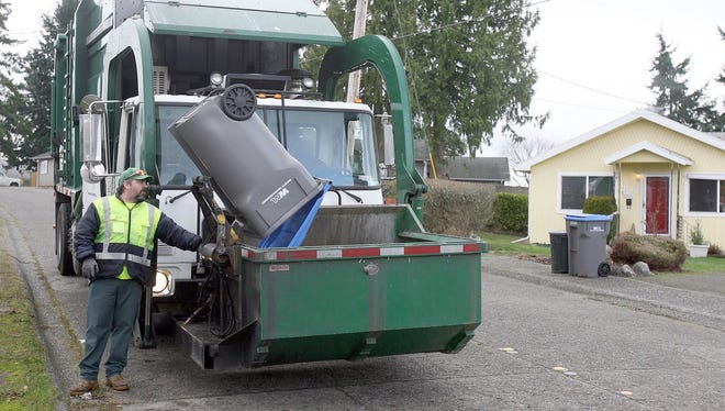Larry Bell of Waste Management dumps a recycling container to unload in his truck in East Bremerton in 2012.