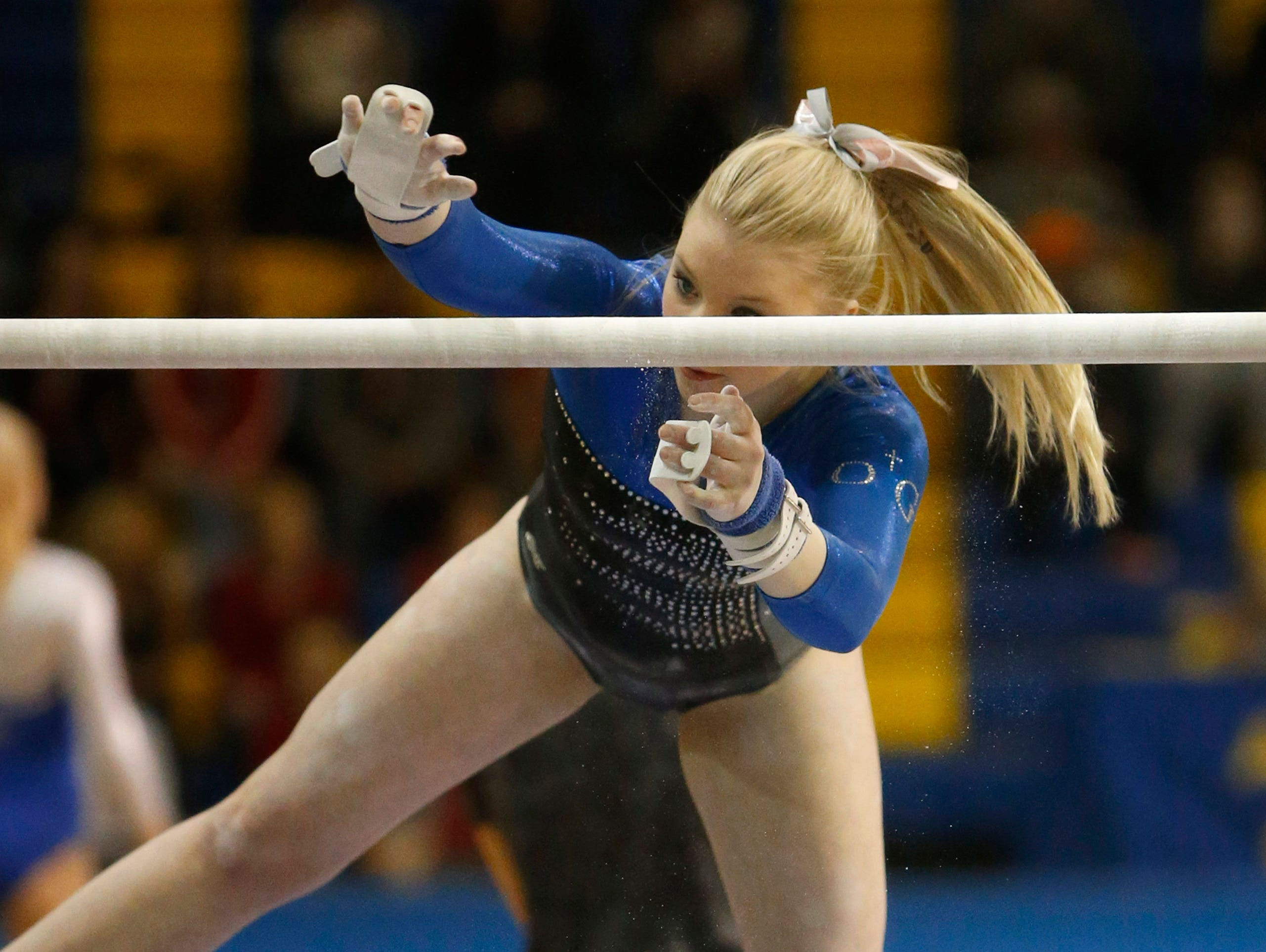 Sioux Falls O'Gorman's Lizzie Miller reaches for the bar during Saturday's individual competition at the Class AA State Gymnastics Meet at the Golden Eagles Arena. American News