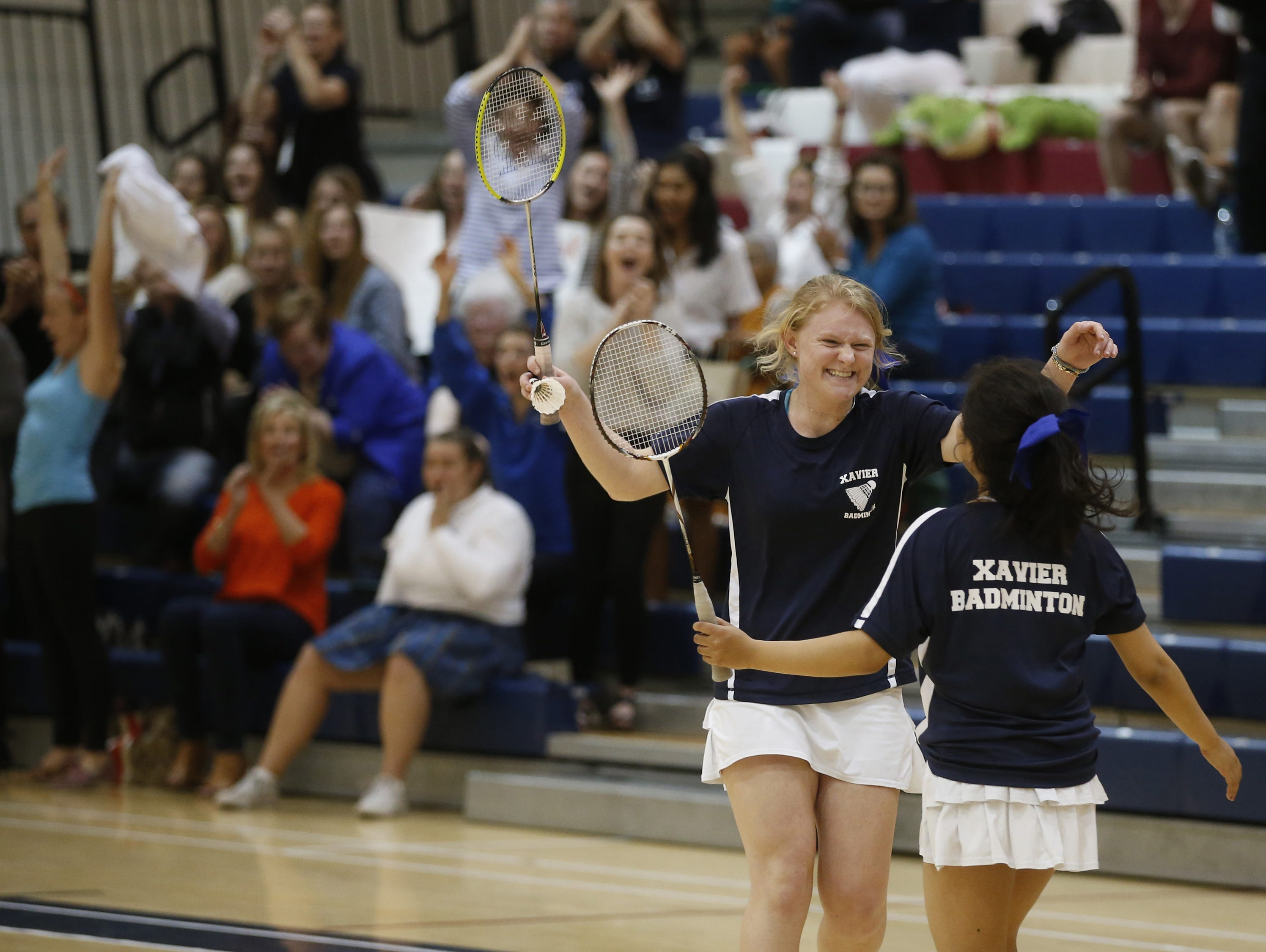 Xavier Katie Russell, left, and Kirielle Singarajah celebrate winning their double match against Mesa Red Mountain during the badminton team state championship at Perry High School on October 30, 2015.