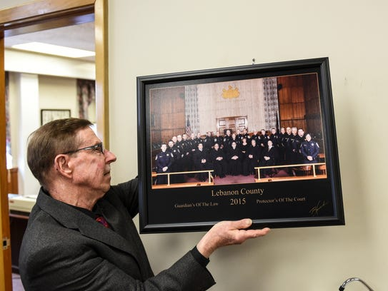 Sheriff Bruce Klingler, hangs the photo after local