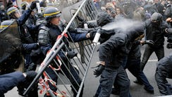 Policemen fight with activists during a protest ahead