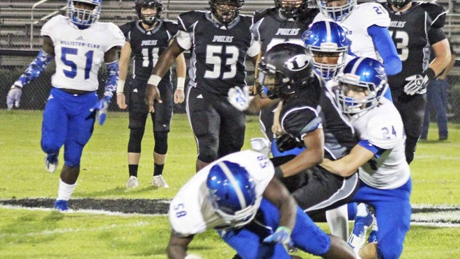 Connor Givens, #24 of the Blue Devils, tackles a Lamar High player in the Nov. 13 playoff game.