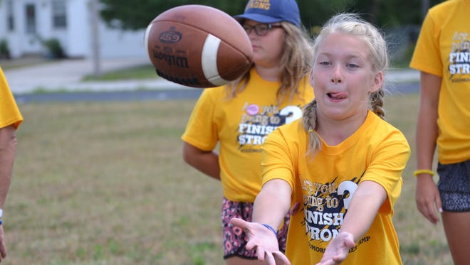 Ella McCarthy catches a ball during the football session at Camp Wildcats. Campers learned skills like passing and catching from Woodmore football players and coach Lou Bosh. The camp not only introduced campers to school sports, but it also exposed students that showed great athletic potential. Ball said a couple of coaches told him they already recognize future sports stars amongst the campers.