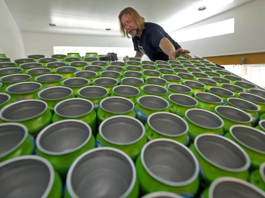In this 2011 photo, Rob Pfeiffer, then-head brewer for Twin Lakes Brewery, helps place empty cans on a distribution machine that fills them with beer. The brewery is moving from its Greenville location.