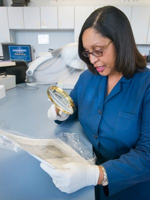 Crime laboratory analyst Kesha White uses a traditional magnifying glass to look over a document at the Florida Department of Law Enforcement (FDLE) in Pensacola on May 23, 2018.  White was recently named the Forensic Scientist of the Year for her work in 2017.