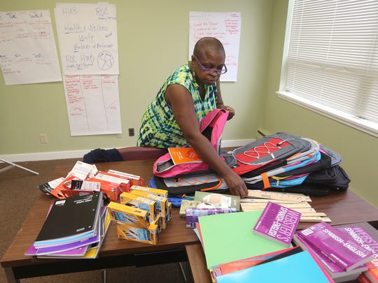 Angela Robinson packs book pages with school supplies at Samaritan Center of Excellence.