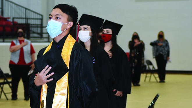 Xeng Yang, Faith Canada, and Hope Canada stand and recite, through masks, the Pledge of Allegiance during Friday's commencement cermony for the Class of 2020 held at Dimaondback Arena.