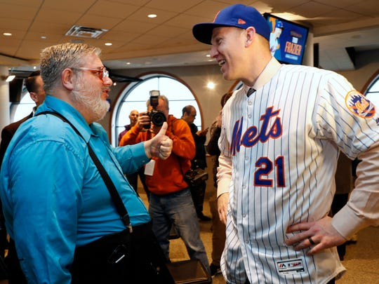 """Gary Dunaier, left, """"The Thumbs Down Guy,"""" gives a thumbs up as he talks to the Mets newly-signed third baseman Todd Frazier after a press conference in which the Mets introduced Frazier to the media, Wednesday, Feb. 7, 2018 in New York. Frazier reportedly signed a two-year deal, finalized on Wednesday. The contract calls for Frazier to be paid $8 million this year and $9 million in 2019."""