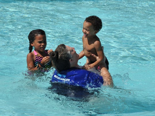 A family enjoys a morning swim after the official ribbon cutting ceremony was held at the new Camp Fire of North Texas swimming pool located in Harrell Park.