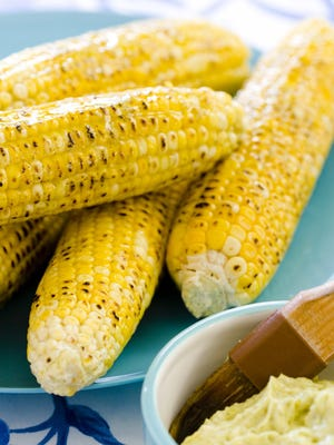 """This undated photo provided by America's Test Kitchen in May 2018 shows grilled corn on the cob in Brookline, Mass. This recipe appears in """"The Complete Cook's Country TV Cookbook,"""" 2017."""
