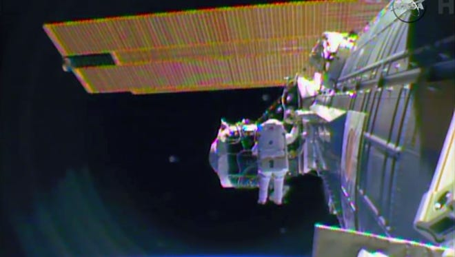 """In this image from television astronaut Barry """"Butch"""" Wilmore begins the spacewalk Saturday morning Feb. 21, 2015 to wire the International Space Station in preparation for the arrival in July of the international docking port for the Boeing and Space-X commercial crew vehicles."""