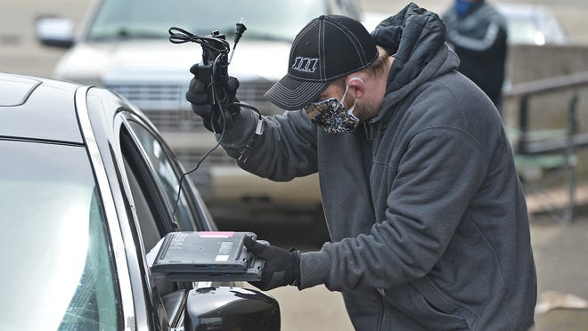 Dan Gibbons, an  information technology technician with the Erie School District, hands two laptop computers and chargers to a driver in a parking lot at Erie High on April 14, during the statewide school shutdown due to the pandemic. The Erie School District is using $2.6 million in federal coronavirus relief aid to purchase laptop computers and iPads for all district students in 2020-21.