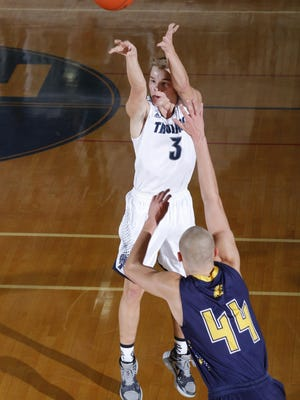 East Lansing's Caleb Hoekstra (3) hits a 3-pointer against DeWitt's Tanner Reha (44) Tuesday in East Lansing.