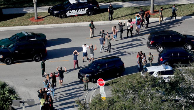 FILE - In this Feb. 14, 2018 file photo, students hold their hands in the air as they are evacuated by police from Marjory Stoneman Douglas High School in Parkland, Fla., after a shooter opened fire on the campus. Newly released reports are providing more details about the law enforcement response to the massacre of 17 people at the high school. The Coral Springs police released reports on Monday, April 16, from several of its officers. (Mike Stocker/South Florida Sun-Sentinel via AP, File)