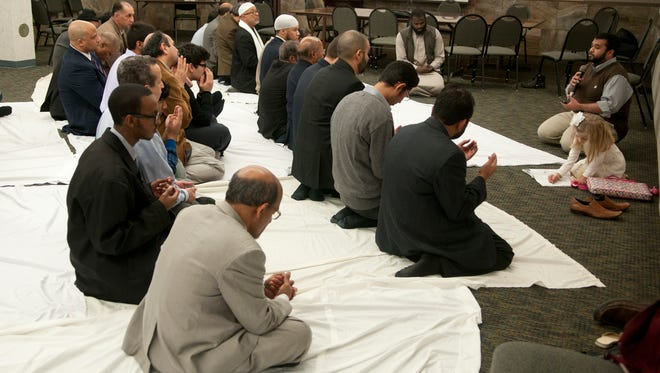 Adil Majid (far right), a member of the Muslim Student Association at Indiana University-Purdue University Indianapolis, leads a prayer of supplication Saturday, Nov. 22, 2014, for slain aid worker Abdul-Rahman (Peter) Kassig during a service at the Indiana Interchurch Center in Indianapolis.