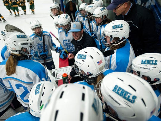 South Burlington girls hockey coach Jake Orr, center, goes over strategy with his team during a timeout in the final seconds of Saturday's 4-3 win over BFA-St. Albans at Cairns Arena.
